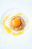 A lightly poached egg yolk on orange polenta
