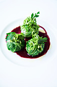 Two types on pointed cabbage on red cabbage broth (stuffed pointed cabbage balls with a pointed cabbage salad)