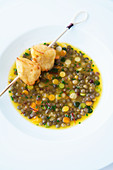 Lentil soup with orange and a potato skewer