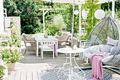weiße Terrasse mit Hängesessel und Sitzgruppe