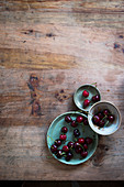Cherries on three green plates at a wooden table