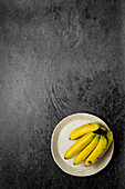 Small bananas on a white plate at a black backdrop