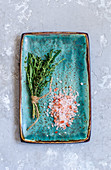Himalayan salt and Provencal herbs on a turquoise-colored kraft plate