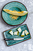 Slices of juicy melon and melon seeds on kraft turquoise plates