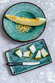 Aufgeschnittene Futuro-Melone mit Kernen auf türkisen Tellern