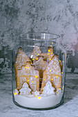 Gingerbread city in a glass jar with lights on a gray background