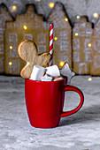 Heiße Schokolade mit Lebkuchenmann vor beleuchteter Lebkuchenstadt