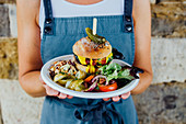 Burger on a plate held by woman