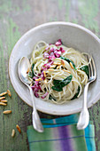 Rice spaghetti with spinach, red onions and roasted pine nuts