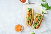Banh-Mi-Sandwich mit gegrilltem Schweinefilet, Karotten, Gurken, Jalapeno und Koriandergrün