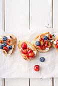 Bruschetta mit Kirschen, Blaubeeren, Honig und Frischkäse