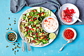 Avocado, courgette, cucumber and quinoa salad with pomegranate, pumpkin seeds and hot yoghurt dressing