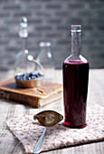 Old, vintage wine bottle with homemade blackcurrant, blueberry and blackberry vinegar.
