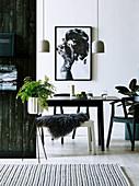 Pendelleuchte über Esstisch und Bank mit Felldecke, im Vordergrund Zimmerpflanze