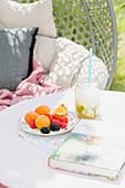 Obstteller und Virgin Caipirinha auf Gartentisch
