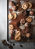 Cookies and muffins on a baking tray surronded by crumbs and chocolate