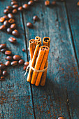 Coffee beans and cinnamon sticks on wood