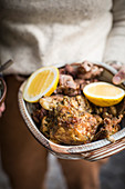 A person holding a bowl of grilled chicken and lemons