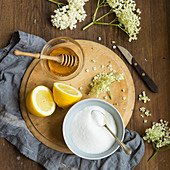 Freshly picked elderflowers on and around a chopping board of the ingredients that go into making elderflower cordial, lemons, honey and sugar