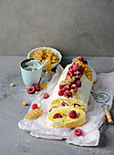 A sponge roll with raspberries and white currants