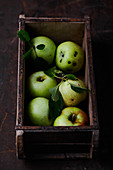 Fresh green apples in a wooden box