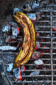 A banana filled with honey on a grill (top view)