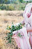 Frau hält Olivenzweige auf dem Feld