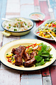 Marinated BBQ lamb ribs with mango cucumber salad