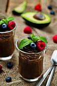 Roh veganer Schokoladen-Avocado-Pudding mit Beeren und Minze