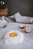 Rohes Ei im Mehlhäufchen auf Marmorarbeitsplatte