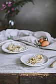 Rohe selbstgemachte Pasta auf Tellern und rustikalem Küchentisch
