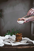 Hands of person pouring honey on chocolate dessert with wooden spoon