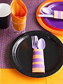 Gedeckter Kindertisch in Schwarz, Orange und Lila für eine Halloweenparty