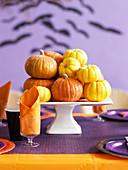 Zierkürbisse auf gedecktem Tisch für Halloweenparty