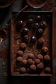 Schokoladen-Orangen-Trüffelpralinen mit Kakaopulver auf Tablett