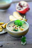 Curry and banana soup with coconut milk and pomegranate seeds