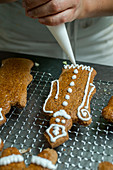 A baker decorating gingerbread men with icing from a piping bag