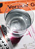 Ein Glas Wasser daneben Tabletten zur Wasserreinigung und Wasseraufbereitung
