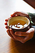 Hands holding a bowl of green tea
