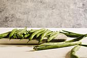 Rohe grüne Bohnen auf Küchenbrett und daneben