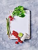 Frische Radieschen, Tomaten, Spargel und Limette auf Schneidebrett