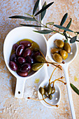 Olives and caper apples in bowls