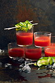 Gazpacho served in glasses with cucumber skewers
