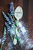 an arrangement of lavender flowers, sugar and a spoon
