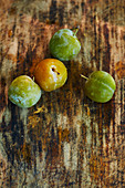 Four greengages on a wooden surface