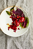 A red salad with pickled eggs in beetroot juice and blackberries (seen from above)
