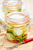 Pickled goat's cheese with lemons, fennel and chilli in glass jars
