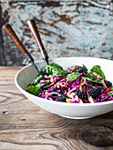 Slaw made with red cabbage, toasted caraway seeds, red onion and spinach dressed with maple syrup dressing