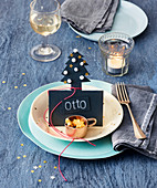 A Christmas table setting with a name card