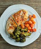 Oven roasted chicken breast with broccoli and carrots (top view)